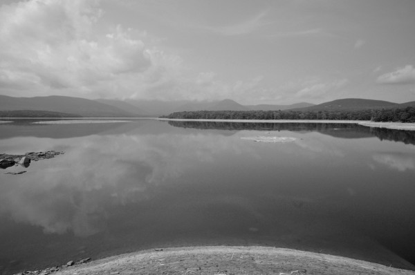 a wide angle black and white view of the Ashokan Reservoir on a humid summer's day.